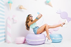 Inspired funny girl wearing tank-top and denim shorts sitting on toy macaroon and making selfie. Laughing young lady in sunglasses and headphones taking picture of herself in room with sweet interior.