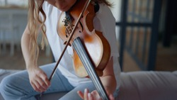 Inspired girl performing music composition on violin with bow. Female musician creating music on string instrument in living room. Young woman playing on musical instrument