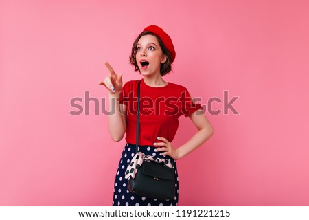 Inspired glamorous woman in elegant attire pointing finger to something interesting. Indoor shot of enthusiastic caucasian girl in french beret and red blouse.