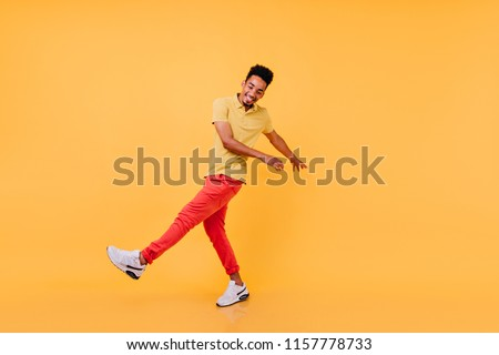 Inspired guy in bright casual attire funny dancing. Laughing african male model in yellow t-shirt and red pants fooling around in studio.