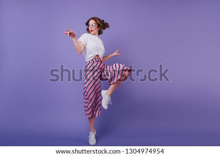 Inspired jocund girl in sneakers dancing on purple background. Gorgeous young female model with dark wavy hair jumping in studio.