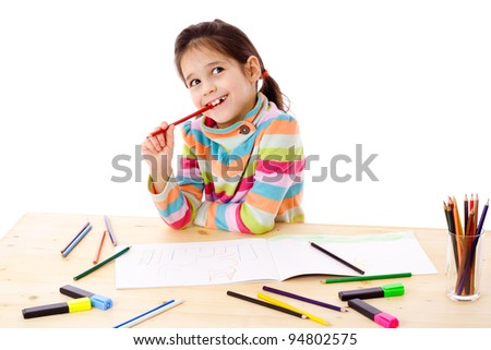 Inspired little girl at the table draw with crayons, isolated on white
