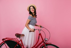 Inspired shapely woman standing on pink background with bicycle and looking away. Blissful brown-haired girl in hat enjoying indoor photoshoot.