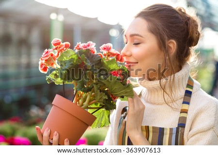 Inspired smiling young woman florist smelling flowers of begonia in greenhouse