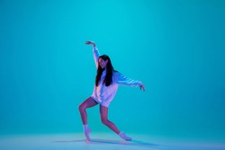 Inspired. Young and graceful ballet dancer isolated on blue studio background in neon light. Art, motion, action, flexibility, inspiration concept. Flexible caucasian ballet dancer, moves in glow.