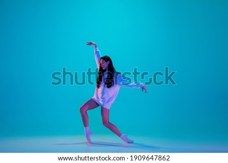 Inspired. Young and graceful ballet dancer isolated on blue studio background in neon light. Art, motion, action, flexibility, inspiration concept. Flexible caucasian ballet dancer, moves in glow. Foto stock ©