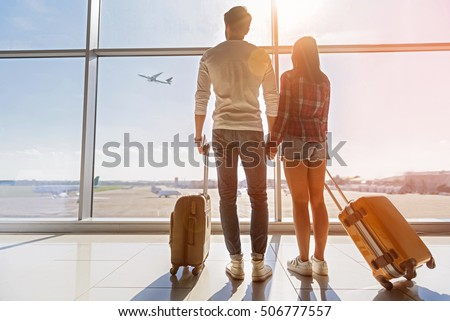 Shutterstock Inspired young loving couple is looking at flying plain in sky. They are standing near window at airport and holding hands