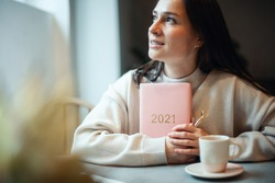 Inspired young woman with a smile looking through window and holding coral colored diary 2021. Hope and inspiration concept. Lady is smiling and dreaming about future new year. Happiness and success.