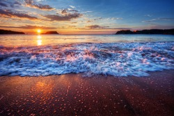 Inspiring and dynamic ocean bay sunrise on a secluded beach with fabulous sand and breaking wave