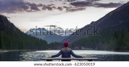 Inspiring image of an adventurer guy watching sunset on the great French Alps mountains. #623050019