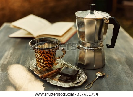 Instagram looking picture of cup of coffee, vintage moka pot, chocolate and cinnamon. Color toned with filters. Selective focus, Shallow Depth of field