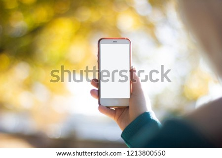 Instagram photography blogging concept. hand holding phone taking photo of autumn landscape