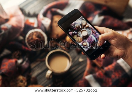 instagram photography blogging workshop concept. hand holding phone taking photo of stylish winter flat lay coffee cookies and spices on wooden rustic background. cozy mood autumn.