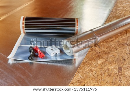 Installation infrared carbon heating film for floor. Heating film roll, termostat and roll for termal insulation lies on OSB floor in room. Electrical floor heating system, radiant heating