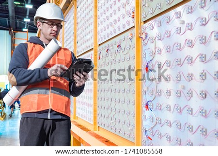 Installation LED lighting. Builder is holding a tablet in his hands. Concept - lighting engineer. Process installing LED screens. Electrician. Concept - installation of electrical panels. LED sales
