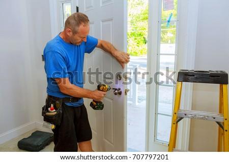 Installation of a lock on the entrance door Hand 's man with screwdriver Installs door knob. #707797201