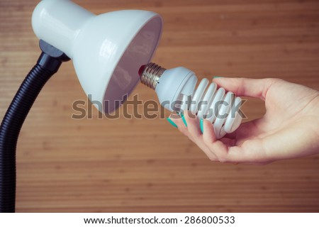 Installation of a modern economical bulb in a table lamp. Female hand holding spiral lamp.