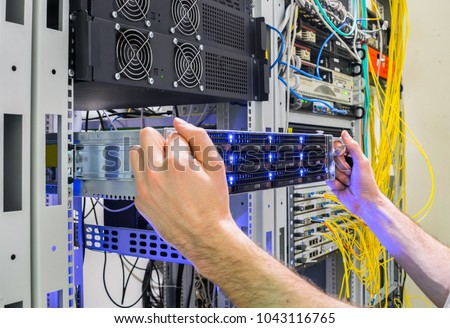 Installation of a new server in a rack with computer equipment. Performing work to replace the server in the data center. The system administrator's hands hold a powerful supercomputer. Stock photo ©