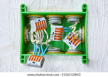 Installation of a plastic junction box for home wiring, electrical wires spliced using a spring terminal block with a push lever for five contacts. Electric wire connector. #1526510843