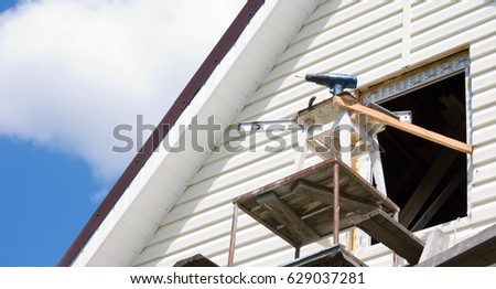 Installation of a siding on a house against the sky #629037281