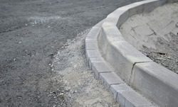 installation of concrete curb into concrete. in the space of the road, which so far has only a concrete base before laying the asphalt layer and rolling.