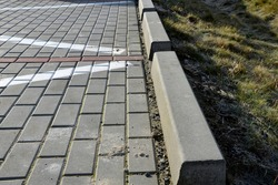 installation of concrete curbs with gaps that let water into the park into the ditch, where it seeps into the grass and does not drain into the sewer, kerbside