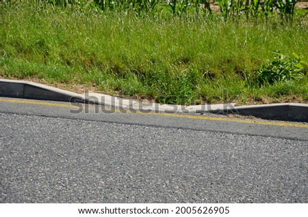 installation of concrete curbs with gaps that let water into the park into the ditch, where it seeps into the grass and does not drain into the sewer, kerbside Stok fotoğraf ©