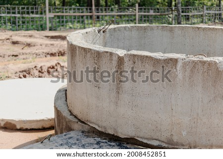 Installation of concrete sewer wells in the ground at the construction site. The use of reinforced concrete rings for cesspools, overflow septic tanks. Improvement of wells and storm sewage Foto stock ©