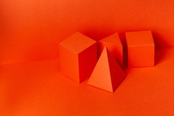 Installation of geometric objects. Multi-colored rectangular shapes cube prism pyramid and cuboid on red background. Minimal geometric still life composition. Platonic solid geometric figures.