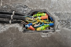 Installation of junction box, high voltage. Using an insulating connection clamp or a twist-in connecting wire nut to connect electrical wires in a distribution on a concrete wall