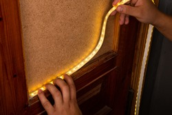 installation of LED strip with warm yellow light on the door for decorative lighting.