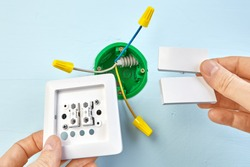 Installation of new button for two-button light switch, round outlet box for wall light on the background.