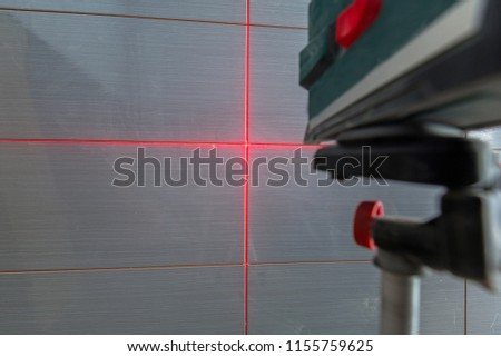 Installation of new tiles on the wall using a laser level