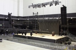 Installation of professional sound, light, video and stage equipment for a concert. Stage lighting equipment is clamped on a trusses for lifting. Line array sound speakers.