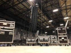 Installation of professional sound speakers, line array, light, video and stage equipment for a concert. Tech zone with flight cases.