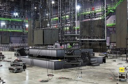 Installation of professional stage, sound, light and video equipment for a tv show. Led screens. Stage lighting equipment is clamped on a trusses. Line array speakers. Flight cases.