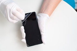 installation of protective cover film on the smartphone. Maintenance support and repairing service concept.