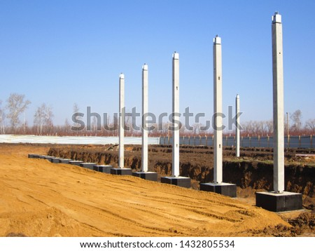 installation of reinforced concrete columns-supports on the supporting foundation in the trench of the plant under construction #1432805534