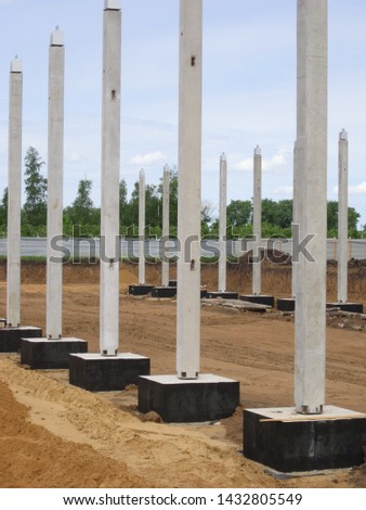 installation of reinforced concrete columns-supports on the supporting foundation in the trench of the plant under construction