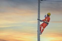 Installation of switching and connecting overhead electrical lines on a pole. An electrician is working on a pole.Linemen.