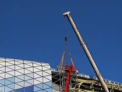 Installation of the football stadium roof section with the help of a construction crane