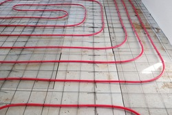 Installation of underfloor heating, laying heating pipes on extruded polystyrene insulation.