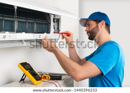 Installation service fix  repair maintenance of an air conditioner indoor unit by cryogenist technican worker with screwdriver  blue shirt and baseball cap