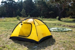 Installed tourist tent and a camping lantern in nature in the forest. Domestic tourism, active summer holidays, family adventures. Ecotourism, social distance. Copy space