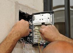 Installer of a new intercom in the entrance door of a apartaments building