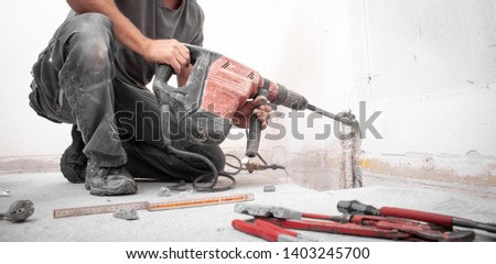 Installer stabs hole with Hilti rotary hammer in the wall on the construction site