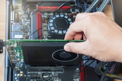 Installing a Graphics Card on the computer motherboard with hand.