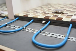 Installing a radiant floor heating system with a close up of heating cables fastened to the floor underlayment under ceramic mosaic bathroom floor while house renovation.