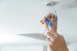 Installing a spotlight in the room. A man is using an insulating tape to the bare electric wires.