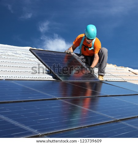 installing alternative energy photovoltaic solar panels on roof #123739609